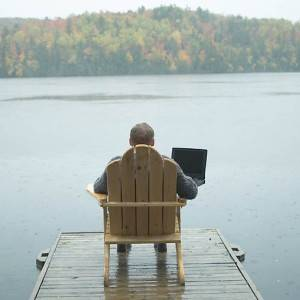 Remote working man with laptop beside lake