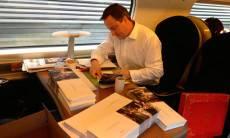 David Cameron signs Christmas cards on a train