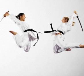 Women fighting with katana swords --- Image by © Ocean/Corbis