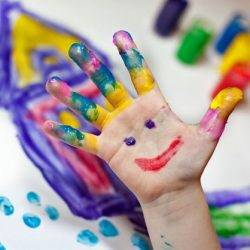 A child's hand shows creativity covered in many paint colours and a smiling face