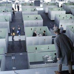 A still from Jacques Tati's film playtime as the protagonist looks out over cubicles in an office