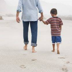 Father and son walk on beach showing need for shared parental leave