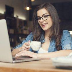 A young woman enjoys flexible working in a cafe