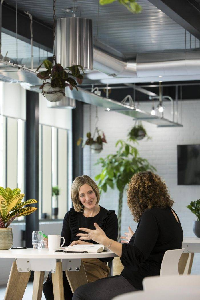 Two women discuss business in an attractive office space
