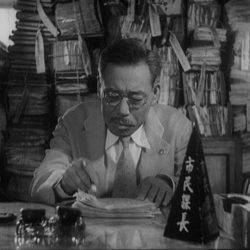 A still from the movie Ikiru in which the protagonist is sitting at a desk