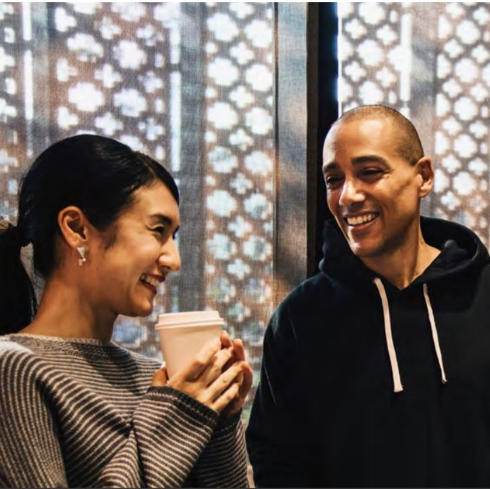 Two people laughing together to illustrate the principle of wellbeing